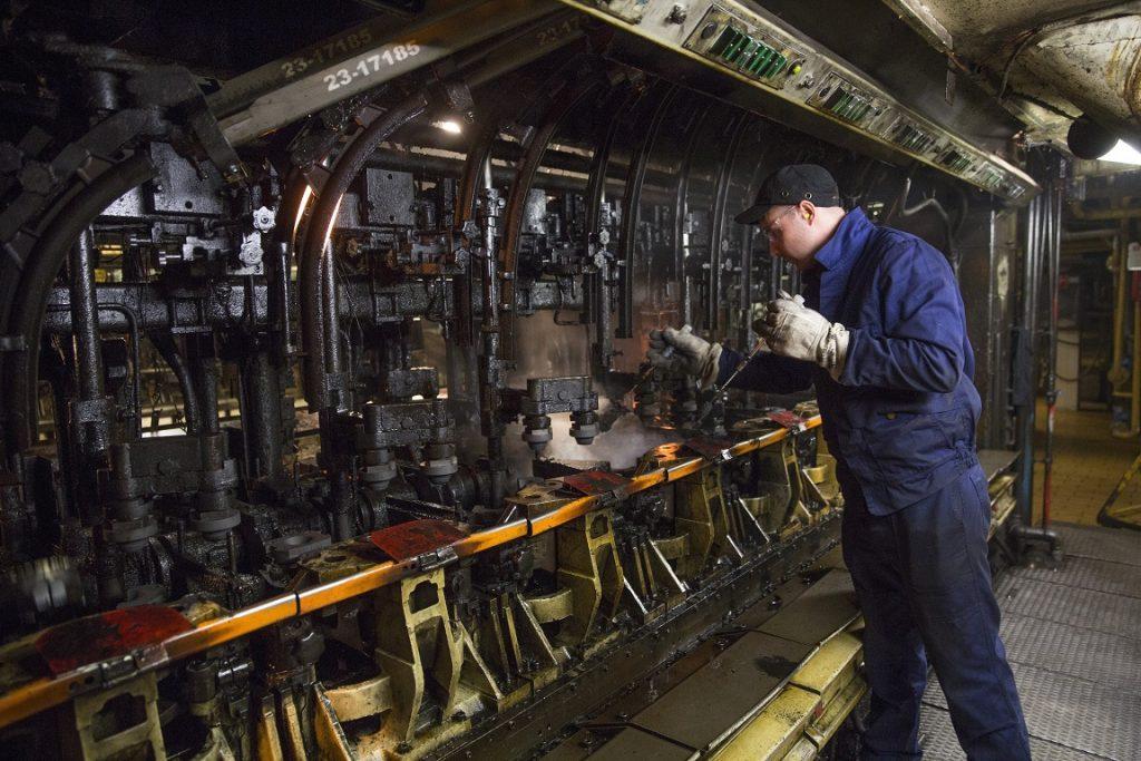 Egy dolgozó az üveggyártó gép formakenését végzi az O-I Magyarország Üvegipari Kft. orosházi gyárában. / MTI Fotó: Rosta Tibor