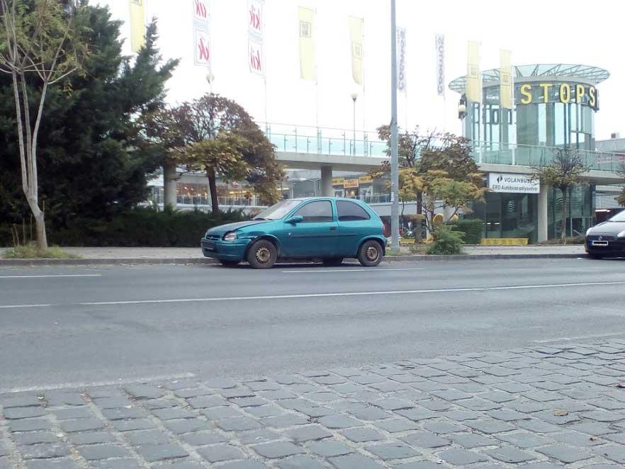 Az autóroncs Érd központjában, háttérben a Stop Shop bevásárlóközpont. / Fotó: hulladekvadasz.hu