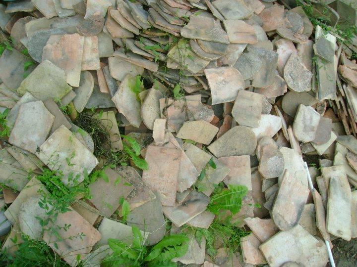 Burkolás hódfarkú cserép eldobálva egy patakpartján. / Fotó: hulladekvadasz.hu