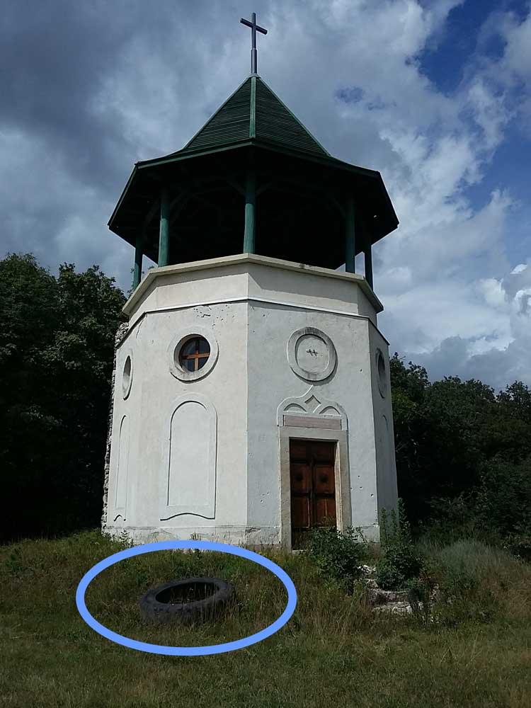 A kápolna oldaldobjára döntött gumiabroncs. / Fotó: hulladekvadasz.hu