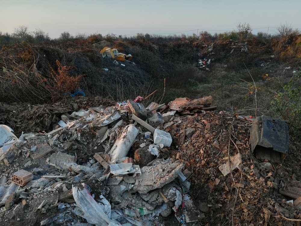 Előttünk építési hulladék, a háttérben bontott hűtők hulladéka színesíti a környezetet.