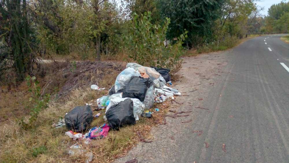 Egy nagy halom kommunális hulladék az vízelvezető árok és az aszfaltos út között.