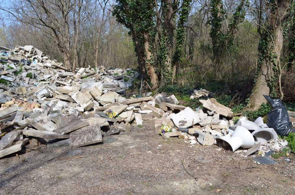 Bontott sírkövek legális hulladéklerakata és a mellé hordott fürdőszobai kellékek (például wc ülőke).
