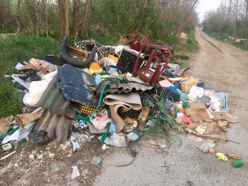 Főként lakossági hulladékból álló hatalmas kupac látható a földút bejáratánál.
