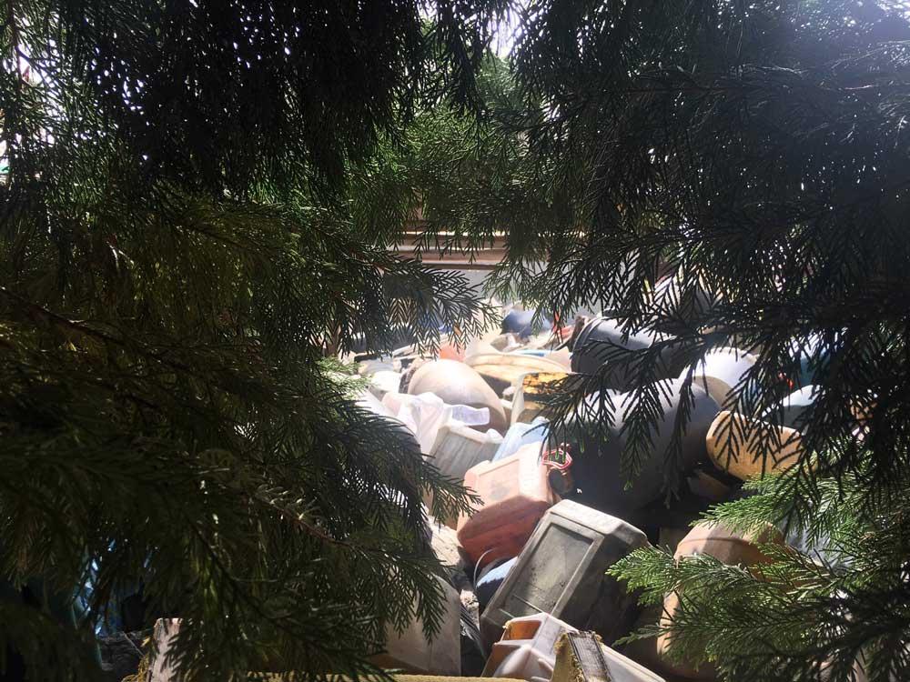 TŰZVESZÉLY!: Közvetlenül a fák és a szomszédos épületek mellett veszélyes hulladéknak minősülő olajos kannák hatalmas mennyiségben.